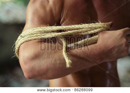young guy pulls rope on hand in abandoned building, fragment