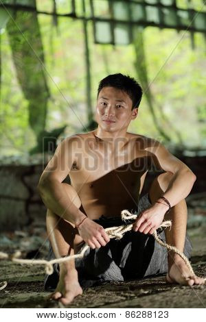 young man in ragged pants sits holding rope in his hands in abandoned building