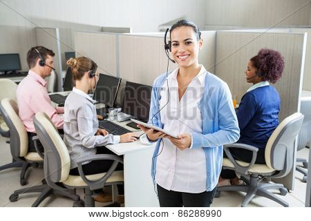 Portrait of happy female customer service representative holding tablet computer while colleagues working in background at call center