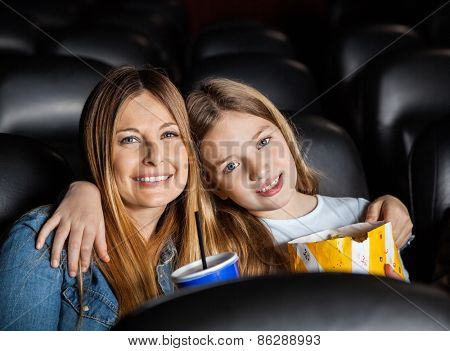 Portrait of affectionate mother and daughter siting in cinema theater