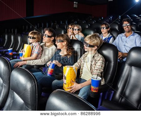 Families of four watching 3D movie together in cinema theater