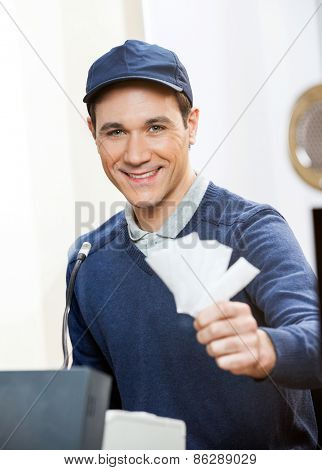 Portrait of smiling male worker holding tickets at box office