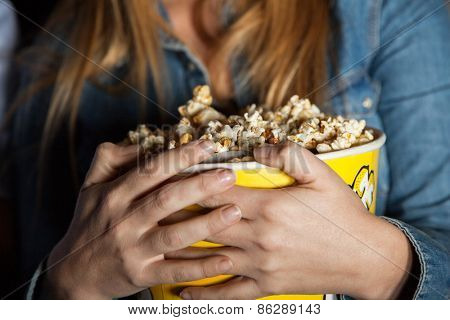 Midsection of woman holding popcorn bucket at cinema theater
