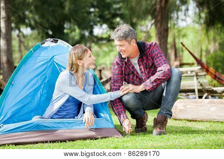 Romantic couple holding hands while setting up tent in park