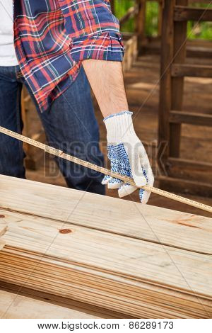 Midsection of male construction worker measuring timber plank with tape