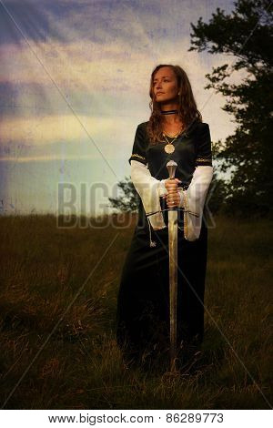Mystical Medieval Woman  Standing  With A Sword On A Wild Meadow With Enchanting Evening Light