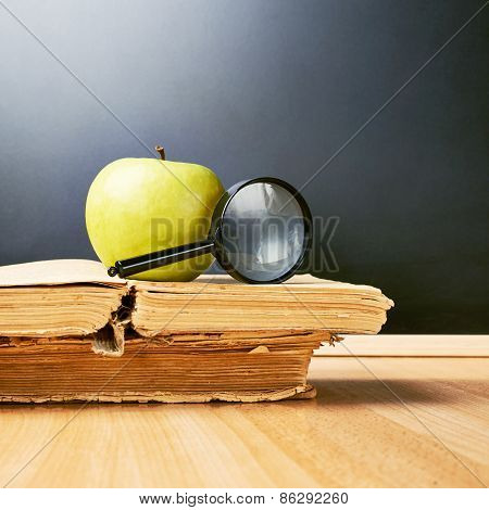 Apple and magnifying glass over the books