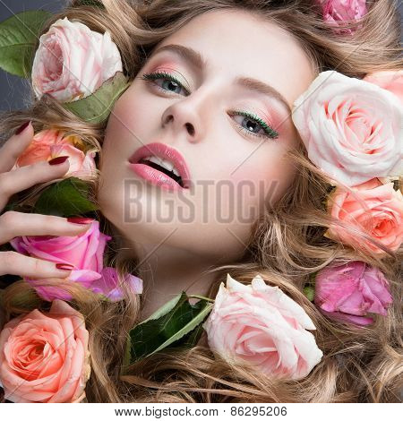 Portrait of a beautiful girl with a gentle pink make-up and lots of flowers in her hair.