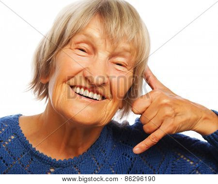 senior happy woman is making a call me gesture, isolated on white
