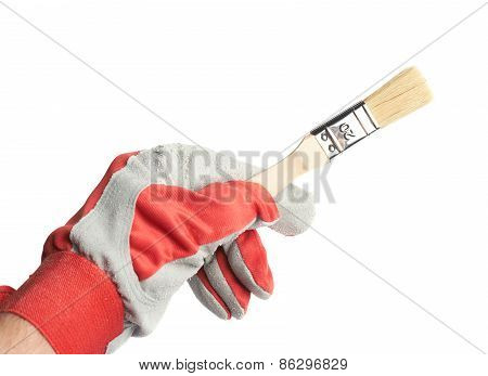 Hand in a working glove holding brush