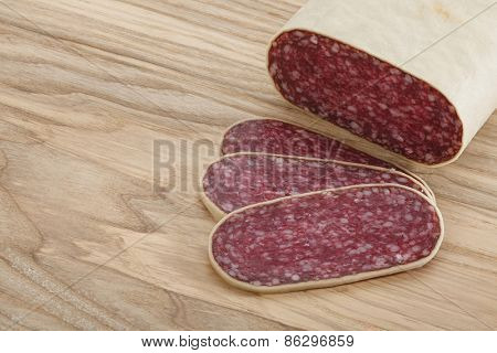Close-up traditional sliced meat sausage salami on wooden board. All in focus.