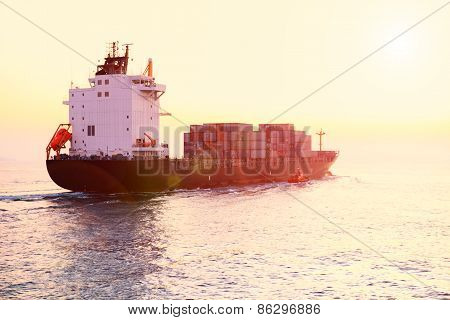 Container Ship Is Sailing Along The Waterway During Sunset.