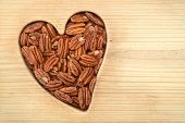 pic of pecan  - a group of pecan halves on wooden flat in heart shape - JPG