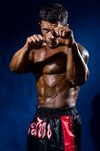stock photo of boxers  - Fighter in a rack with fists on a blue background - JPG