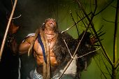 foto of vicious  - Vicious werewolf with a skin on his shoulder and long nails among tree branches - JPG