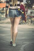 foto of swag  - Beautiful and sexy street girl walking with her skateboard under her arms - JPG