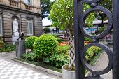 stock photo of scrollwork  - Behind the iron gate is the garden pathway into the National Theater in San Jose - JPG