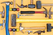 stock photo of carpentry  - Display of a diversity of hammers in a tool kit for DIY carpentry construction mallets and a sledgehammer in a neat arrangement on a wooden table overhead view - JPG