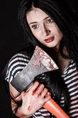 foto of bloody  - Young woman with a big bloody axe over black background - JPG