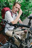 image of forehead  - tired man with bike wipe the forehead at the park bench - JPG