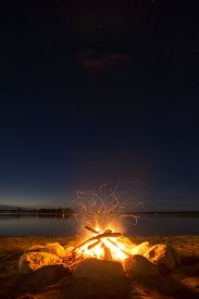 stock photo of sparking  - Sparking camp fire beside lake under a starry sky - JPG