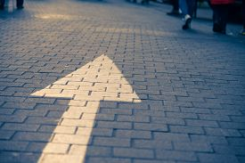 pic of arrow  - Arrow sign on the street go straight with many walking people vintage tone - JPG