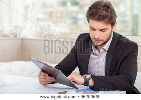 Cheerful young businessman is preparing for meeting
