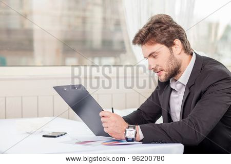 Attractive young businessman is preparing for meeting with client