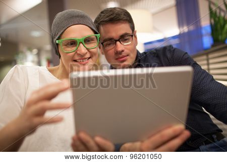 Man and woman using electronic tablet in the restaurant