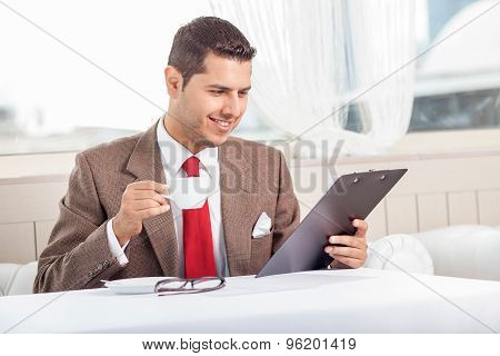 Handsome young man is reading some documents