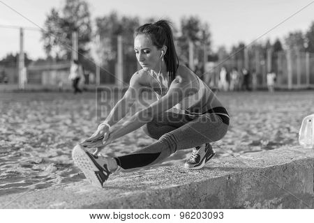Athletic woman stretching her hamstring, legs exercise training fitness before workout outside on a