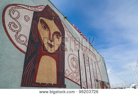 Face Of Local Woman With National Patterns On The Wall.