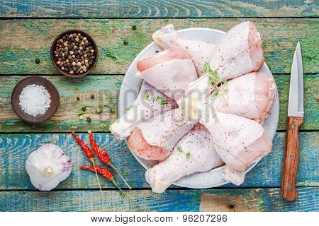 Raw Organic Chicken Legs In Bowl With Thyme, Salt And Pepper