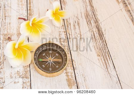Close Up Compass And Tropical Plumeria Flower On Wooden Table