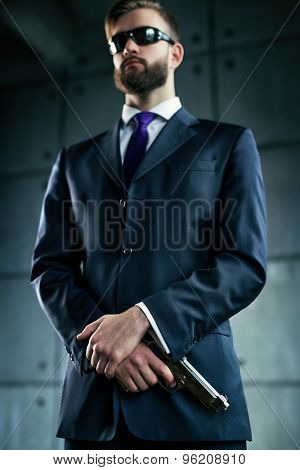 Danger man agent with gun and sunglasses. Focus on hands and gun.