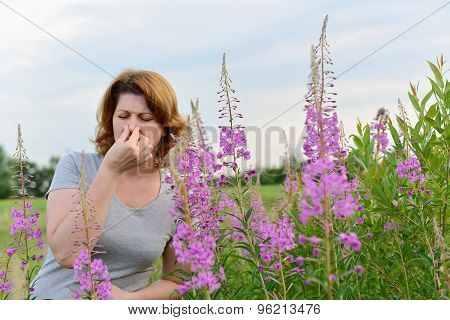 Portrait of  woman with allergic rhinitis near willow-herb in the field