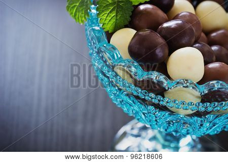 Chocolates In A Glass Bowl On A Black Wooden Background. Festivals And Events.