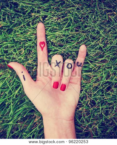 a young girl's hand with lettering i heart x o u written on it in the grass during summer making the rock on sign toned with a retro vintage instagram filter effect app or action