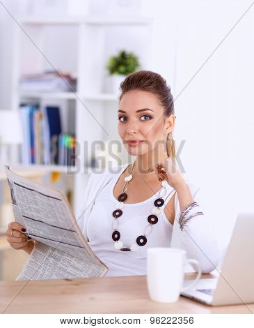 Cute businesswoman holding newspaper sitting at her desk in office