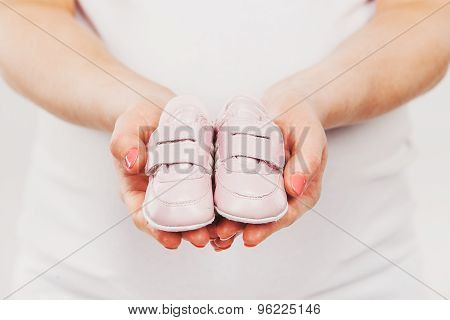 Pregnant woman belly holding pink baby booties, expecting girl. Healthy pregnancy. Maternity and new