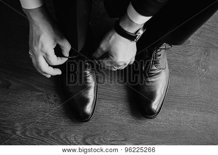 Business man dressing up with classic, elegant shoes. Groom wearing shoes on wedding day, tying the