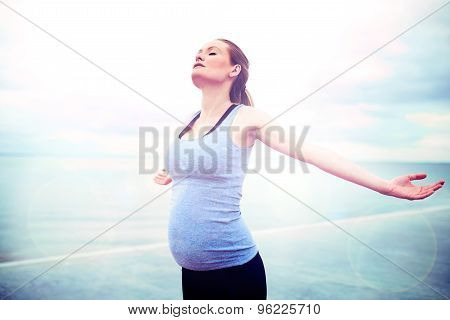 Pregnant Woman Embracing The Sunshine