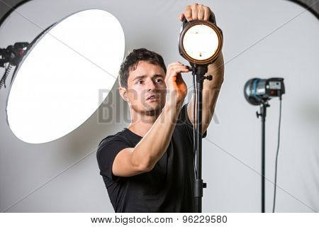 Young, pro photographer setting lights in his well equipped studio before a photo shoot (color toned image; shallow DOF)