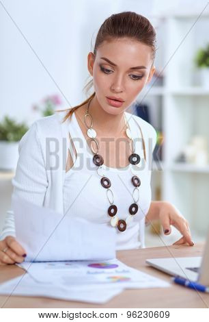 Portrait of a businesswoman sitting at a desk with a laptop .