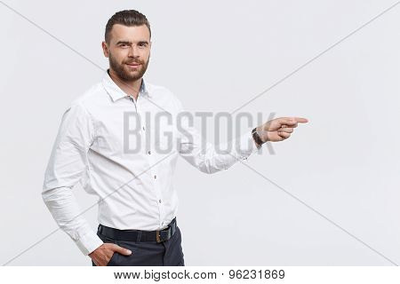 Businessman pointing aside with hid index finger