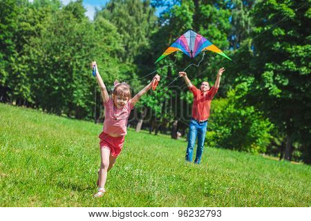The Girl And Her Father Play With A Kite.
