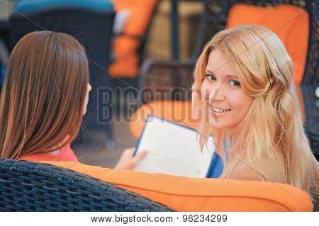 Two girls in cafe looking through menu