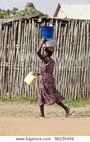 TORIT, SOUTH SUDAN-FEBRUARY 21, 2013: Unidentified South Sudanese woman carries multiple items on her head in the village of Torit