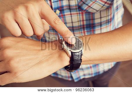 closeup of a young caucasian man tapping his forefinger on his wristwatch