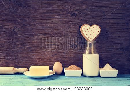 a heart-shaped cookie and the ingredients for cook it, such as milk, eggs, flour, butter and sugar on a blue rustic wooden surface, with a filter effect